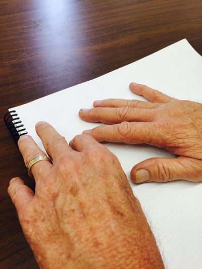 Darell reading Braille with two hands