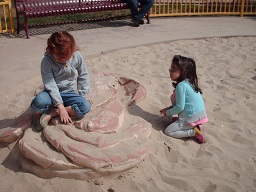 two children playing in the sandbox at park day