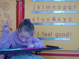 a child reading in front of the Braille wall at Fairmount park