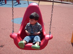 A child swinging on a special safety harness swing at the sensory playground at Fairmount park