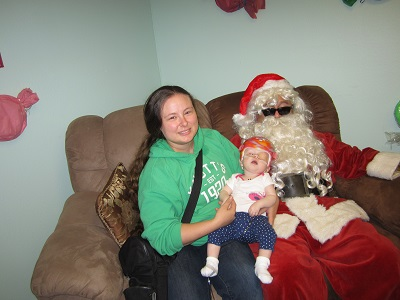 A close up of a Mother and her baby with Santa