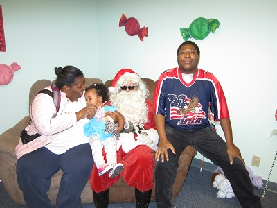 A family sittng with Santa on a couch