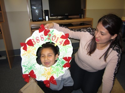 a child sticking her face out of a Christmas Wreath