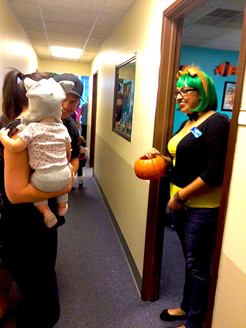 A cat is in the hallway handing out candy.