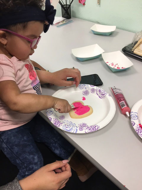 A child is decorating a heart shaped cookie