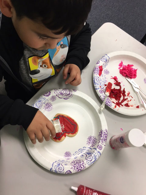 A child is decorating a heart shaped cookie with red sprinkles