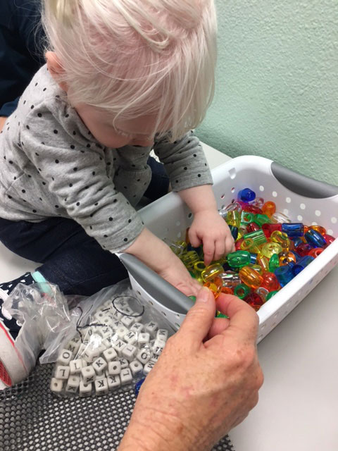 A child is digging through colorful beads to attach to the tactile story board