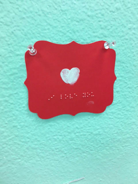 A red valentine with a white heart and Braille that says -'I love you'.