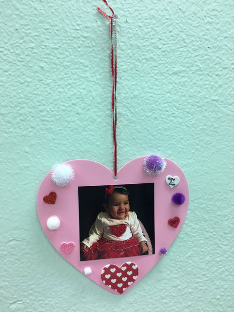 A pink tactile valentine with a picture of a baby