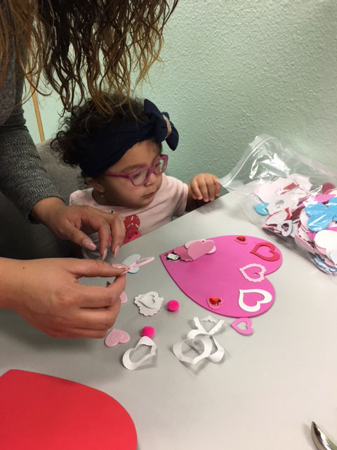 A mother and her child are making a tactile Valentine card