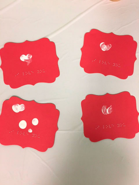 4 red valentine cards with white hearts and Braille that says -'I love you'.