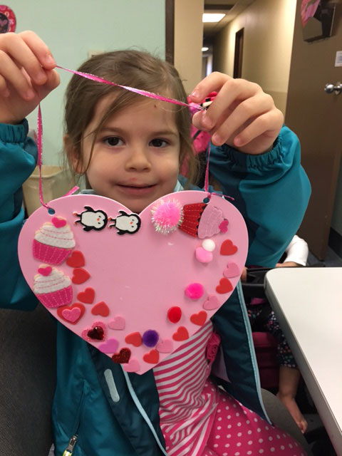 A child is holding up a pink tactile Valentine with shapes and hearts