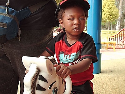 A blind child playing on a rocking horse