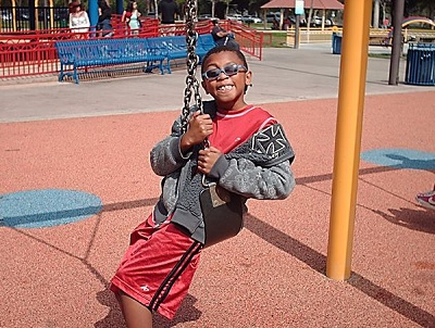 a teen playing on the swings at the sensory playground