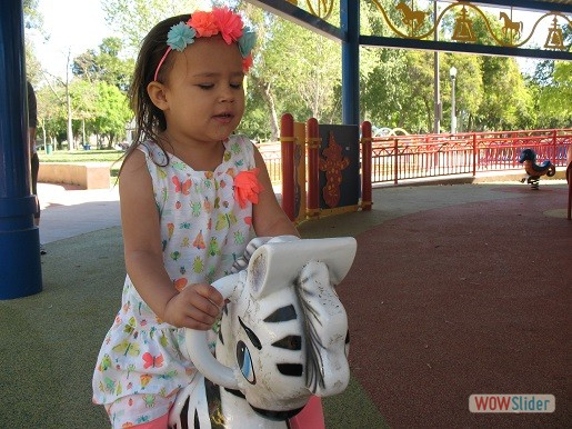 a little girl is on the rocking horse