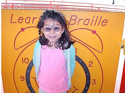 a child standing in front of the Braille Wall
