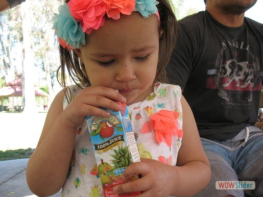 a girl is enjoying her juice at park day