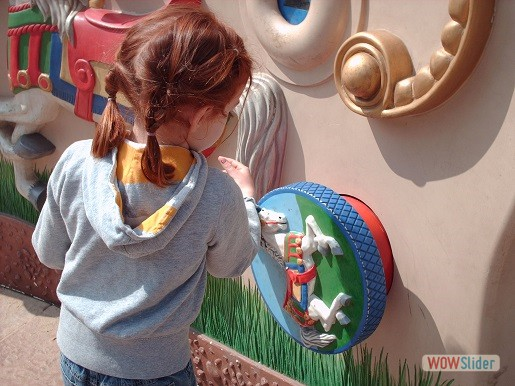 a little girl is standing in font of the tactile wall