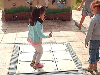 a child stepping on the musical steps at the sensory playground