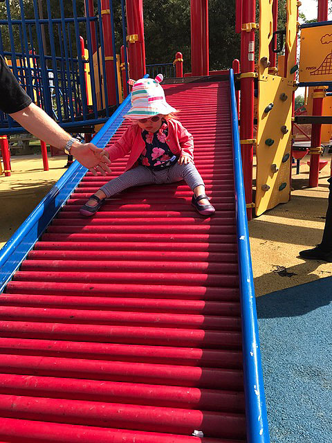 A child is sliding down the slid at the sensory playground at Fairmount Park