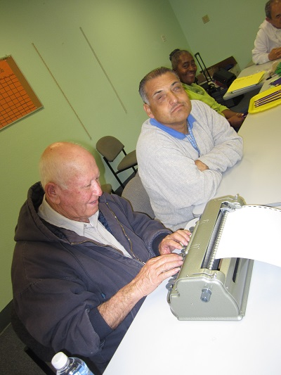 Ramiro learning to type Braille with Ciro.