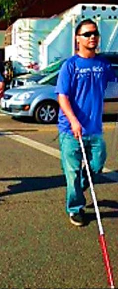 A blind man walking in an intersection using his white cane