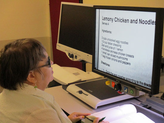 A blind student using a CCTV to magnify a chicken recipe