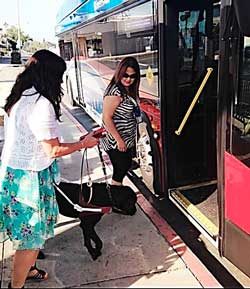 A blindness support mobility instructor takes a blind woman onto a bus with her guide dog.