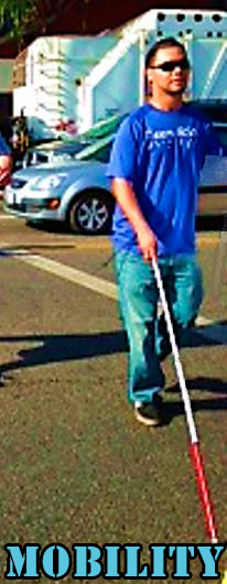 A blind man walks across the street using his white cane.