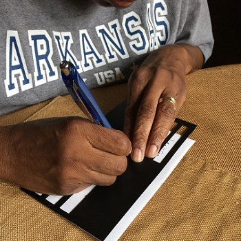 An elderly blind man is signing his name using a writing guide